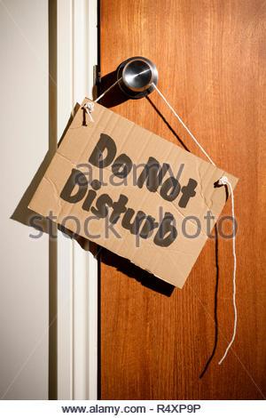 Do Not Disturb written on a makeshift sign hanging on the door handle, Dorset, England. - Stock Photo