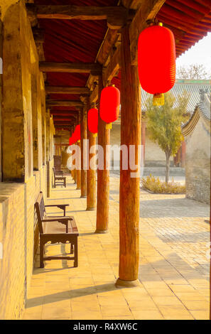 Red lanterns hung under a long wooden porch in Pingyao, China - Stock Photo