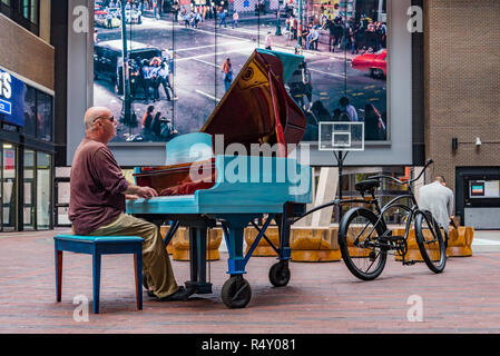 Man plays bicycle towed,  Keys to the Streets Piano, Woodward's Atrium, Vancouver,  British Columbia, Canada - Stock Photo