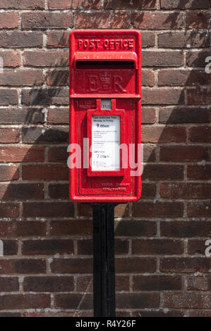 UK red post box next to a brick wall - Stock Photo