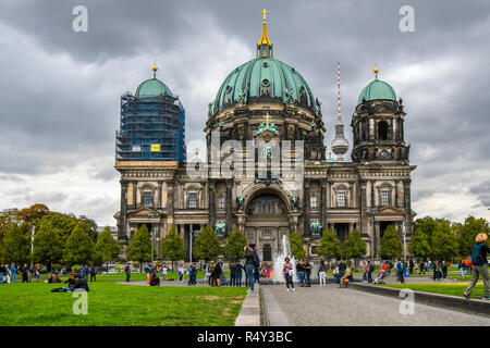 Tourists and locals congregate at the fountain at the Lustgarten, a public green space located in front of the Berlin Cathedral on Museum Island in Ge - Stock Photo