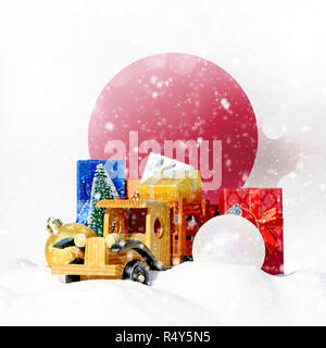 Christmas background.Toy truck with gifts, New Year fir, balls in the snowdrift and Japanese flag - Stock Photo
