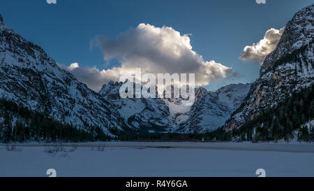 Evening in the winter mountain valley, alpie slope illuminated by reflected sunlight - Stock Photo