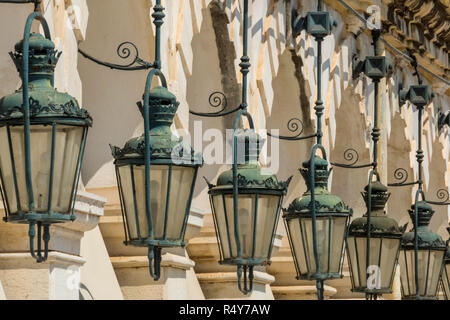 a line or row of decorative victorian style street lights on the side of a classical building in town of kerkyra on corfu in greece - Stock Photo