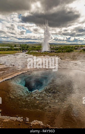 A geothermal pool at The Geysir Hot Spring Area, in the Golden Circle route, in Iceland. The Strokkur geyser erupting in the background. - Stock Photo