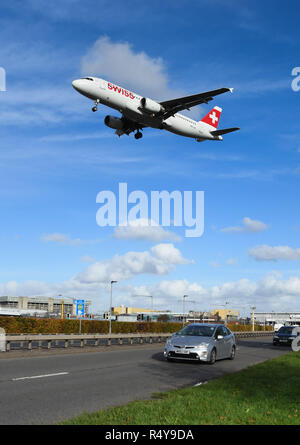 LONDON, ENGLAND - NOVEMBER 2018: Swiss airliner coming into land at London Heathrow Airport passing over traffic on the A30 dual carriageway. - Stock Photo