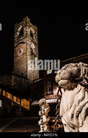 close up of the lion of the Contarini fountain with in the background the Campanone of Città Alta in Piazza Vecchia in Bergamo, vertical night image - Stock Photo