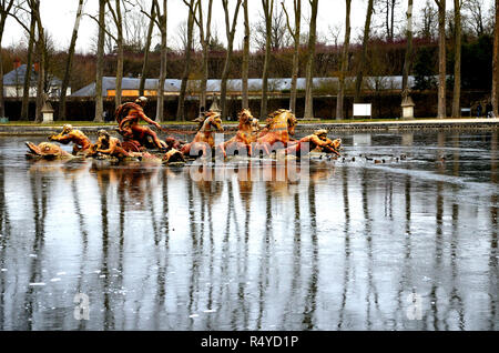 Fountain of Apollo, Palace of Versailles. On a frozen water, reflection of the fountain of Apollo with trees on a winter day. - Stock Photo