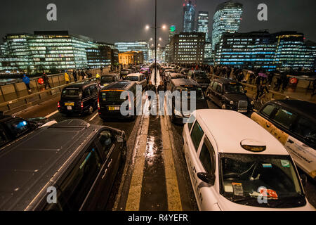 London, UK. 28th Nov, 2018. Black cabs block London Bridge for a third night, and despite miserable weather, as part of their Licensed Taxi Protest against TfL's decision to block them from driving where buses are allowed - such as in Tooley Street and Bnak Junction. Credit: Guy Bell/Alamy Live News - Stock Photo