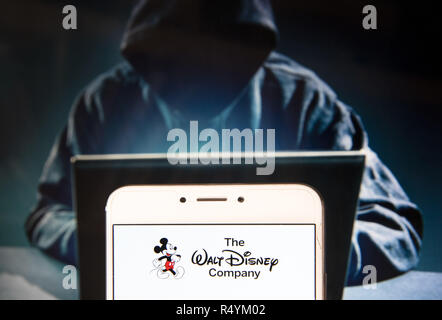 Hong Kong, China. 22nd Nov, 2018. American multinational mass media and entertainment The Walt Disney Company or also called Disney logo is seen on an Android mobile device with a figure of hacker in the background. Credit: Miguel Candela/SOPA Images/ZUMA Wire/Alamy Live News - Stock Photo