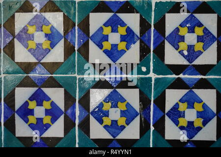 Portuguese traditional painted tin-glazed ceramic tiles Azulejos decorated with contrast blue, green and black squares and yellow details, Lisbon, Por - Stock Photo