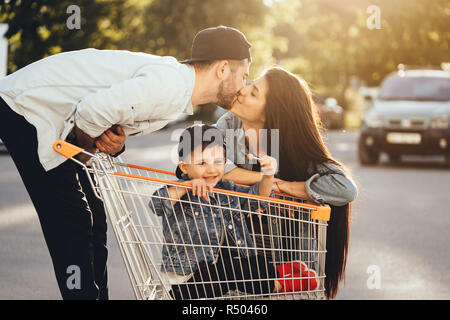 Young parents put their son in a cart and have fun in the parking. - Stock Photo