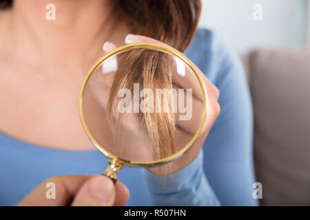 Woman Looking At Her Hair Through Magnifying Glass - Stock Photo
