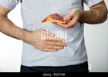 Man With Hand On Stomach Holding Pizza Slice - Stock Photo