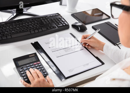 Businesswoman Using Calculator While Calculating On Invoice - Stock Photo