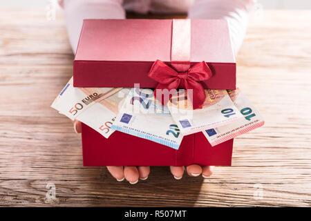 Woman Holding Gift Box Of Us Euro Bills - Stock Photo