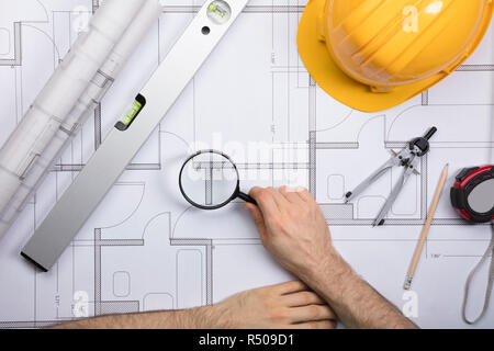 An Engineer Examining The Architectural Blueprint - Stock Photo