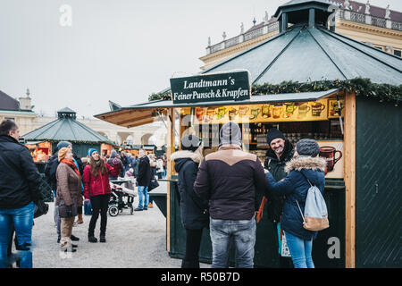 Vienna, Austria - November 25, 2018: People socialising inside Christmas and New Year's Market at Schönbrunn Palace, one of the most important archite - Stock Photo