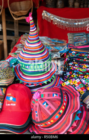 A selection of colourful local merchandise, hats,scarves,bags, and souvenirs for sale on market stall - Luang Prabang, Laos, Lao - Stock Photo