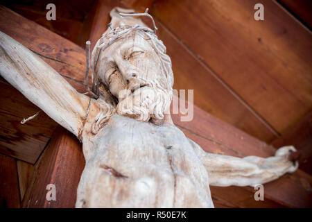 Holy Crucified Jesus Christ close-up. Ancient wooden sculpture. - Stock Photo