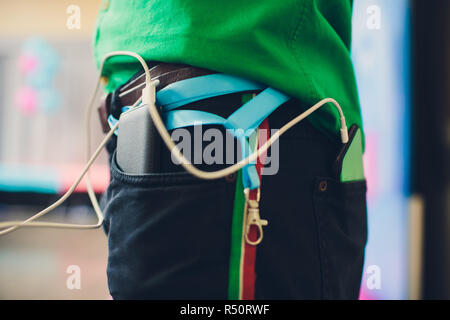 power bank lies in a back pocket of jeans, in the other is a mobile phone that is charged. - Stock Photo