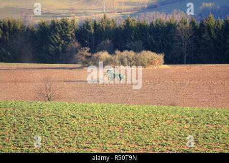 Tractor working on the farm, a modern agricultural transport, a farmer working in the field, fertile land, tractor on sunset background, cultivation o