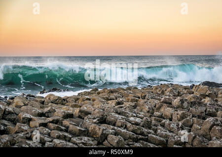 This picture was taken at sunset.  It is of a wave hitting the Giants Causway in Northern Ireland. - Stock Photo