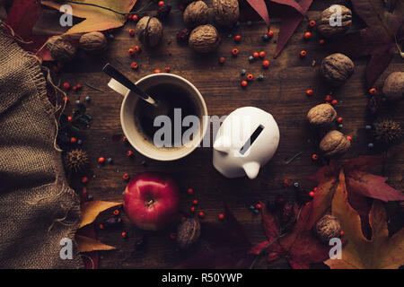 Piggy coin bank with autumn decoration arrangement on wooden table, flat lay top view retro toned - Stock Photo