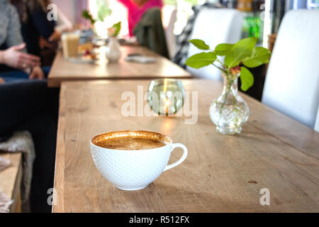 A white cup of cappuccino coffee on a large wooden table with people in the background at a coffee shop in Leknes, Norway. - Stock Photo