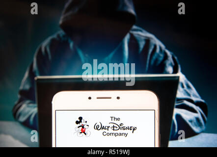 American multinational mass media and entertainment The Walt Disney Company or also called Disney logo is seen on an Android mobile device with a figure of hacker in the background. - Stock Photo