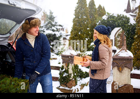Couple unloading freshly cut down Christmas tree and gift boxes out of car trunk to decorate home. Happy man and woman prepare for New Year holidays together. Snowy winter weather outdoors. - Stock Photo
