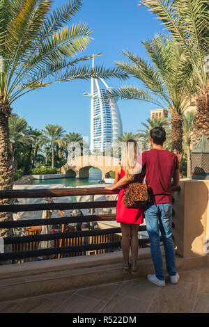 DUBAI, UAE - NOV 12, 2018: Burj al Arab seen from Madinat Jumeirah by young tourist couple. Beautiful view of a beautiful destination for vacation