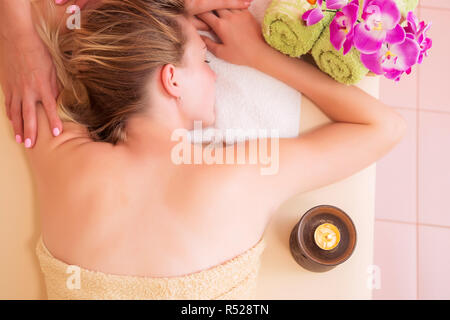 Close up portrait of a young woman getting spa treatment. Head massage. Relaxed woman on massage table receiving beauty treatment at day spa - Stock Photo