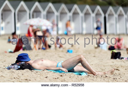File photo dated 24/08/18 of a man sunbathing on Branksome Chine Beach in Bournemouth. Heatwaves linked to climate change pose an increasing danger that threatens to overwhelm health services around the world, a hard-hitting report has said. - Stock Photo