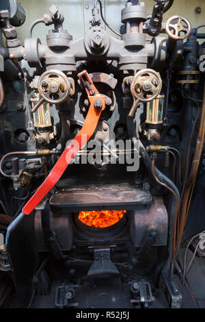 Steam locomotive driver cabin with fire box / firebox & drivers controls / dials & levers in the drivers cab of historic train engine number 41298, running on the Isle of Wight steam Railway line. UK (98) - Stock Photo