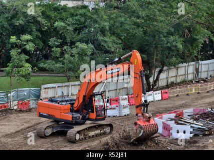 An excavator clears up cropped branches in an area for the expansion of an urban public park, Sham Shui Po, Hong Kong - Stock Photo