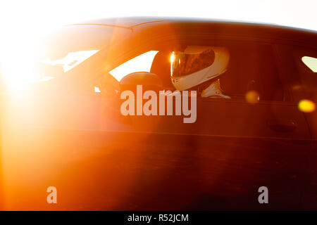A Helmet Wearing Race Car Driver In The Early Morning Sun Looking At His Car Before Starting - Stock Photo