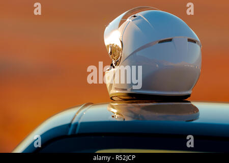 A Racing Helmet Sitting On Top Of A Car at the track In The Early Morning Sun - Stock Photo