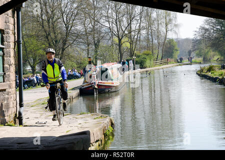 Cyclist riding on towpath next to canal Cromford Matlock Derbyshire England - Stock Photo