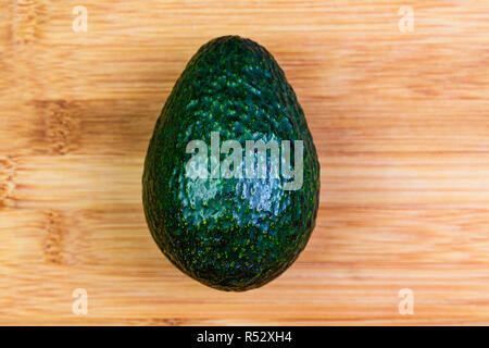 a single whole Hass Avocado on a bamboo  cutting board ready to be sliced, peeled and used in a dish, a salad or eaten alone. - Stock Photo