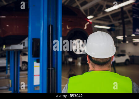 customer looks at work in a car workshop wheel under car in service - Stock Photo