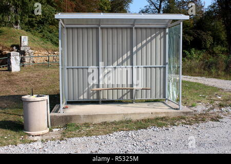 Bus station with metal frame and broken glass next to concrete garbage can surrounded with gravel road and high trees in background on warm sunny day - Stock Photo