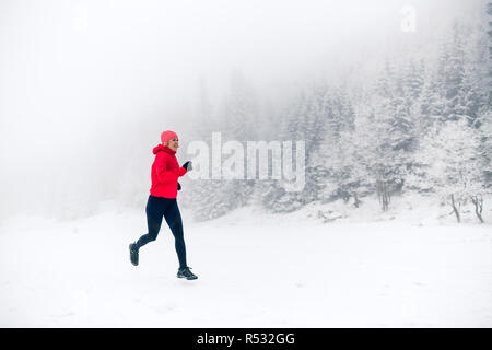 Woman trail running on snow in winter mountains and forest. Sport, fitness inspiration and motivation. Young happy girl athlete working out on snow, w - Stock Photo