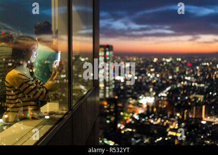Woman visit the observatory and taking photo of the sunset in Tokyo city - Stock Photo