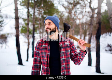 Bearded hipster man in a winter snowy forest with axe on a shoulder. Woodman standing in the forest. Male inspecting trees in woods. Lumberjack woodcutter holding ax wearing plaid red shirt. - Stock Photo