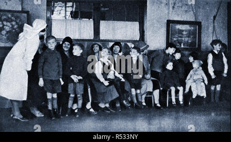 1934- School children in Britain wait to attend one of the new school dental clinics. A school nurse chats to the mothers and children. - Stock Photo
