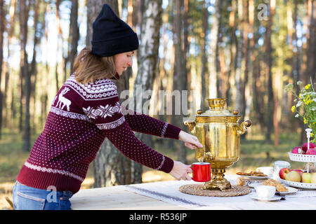 Young woman wearing warm jersey pouring some tea using vintage samovar at the forest - Stock Photo