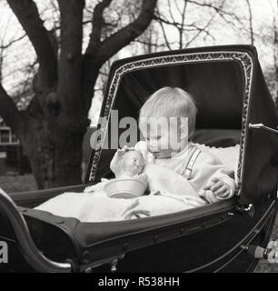 1960s, historical, a small child sitting up in a baby carriage or coach built pram playing with their plastic toy, England, UK. With their wide hood and strong, sturdy chassis, traditional prams like these were very comfortable for the child and who when sitting up, saw the child face the mother which meant plenty of eye contact, which was good for the child's development, - Stock Photo