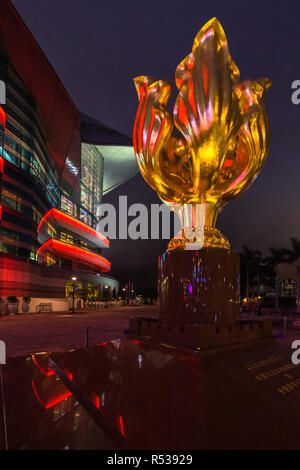 Night view of the Golden Bauhinia sculpture, the emblem of Hong Kong flag. It was built to mark the 1997 handover from Britain to China - Stock Photo