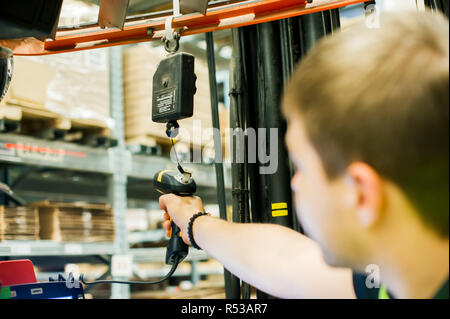 young man in working clothes, driver Reachtruck busy working on the logistics warehouse store - Stock Photo